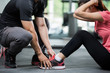 Trainer holding a woman in the leg exercise by Sid-ups.