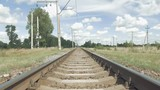 Railroad track in countryside in perspective on blue sky background. View from ground of train tracks and flying butterflies in sunny summer day.