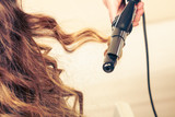 Fototapety Stylist curling hair for young woman.