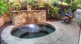 Irvine, CA, USA – August 19, 2016: Oval hot tub spa with waterfall and feng shui garden decor located in a private small patio with plants and flowers.
