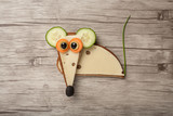 Mouse made of bread and cheese on wooden background