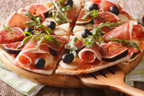 Sliced pizza with figs, ham, cheese and arugula close-up. horizontal