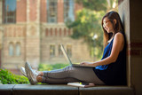 Fototapety College student studying on campus outdoor with laptop casual lifestyle