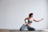 Young woman doing yoga exercise on mat.