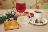 Romantic Birthday Healthy Breakfast.Cup of Coffee and Glass of Red Drink.Wish Card with Flowers.Present in Golden Box.Selective Focus