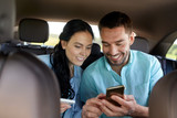 Fototapety man and woman with smartphones driving in car