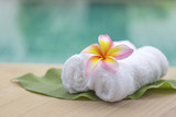 White hand towel roll with plumeria flower at spa pool