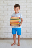 Small intelligent boy holding a pile of book