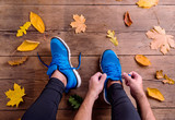 Unrecognizable runner in sports shoes tying shoelaces. Autumn le