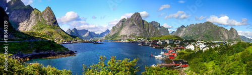 Reine in Lofoten Islands, Norway, with traditional red rorbu huts under blue sky with clouds.