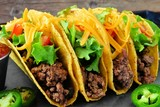 Group of hard shelled tacos with ground beef, lettuce, tomatoes and cheese close up - 118849179