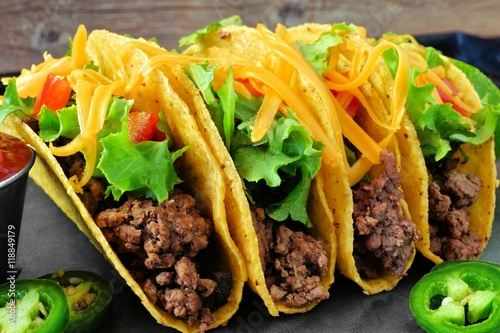 Group of hard shelled tacos with ground beef, lettuce, tomatoes and cheese close Plakát