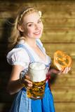 junge blonde Frau im Dirndl mit Bier und Brezn