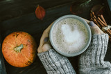 Woman Hands with Spicy pumpkin latte on a wooden board with a sw