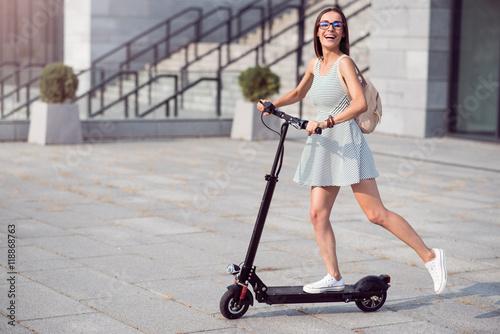 Poster Joyful woman riding a kick scooter