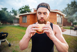 Young bearded hipster guy looking at delicious burger