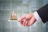 Hand holding business card with miniature building model.