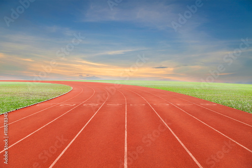 Poster Baksteen Running track with green grass and blue sky white cloud backgro