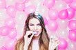 Cute young woman with unicorn horn eating colorful marshmallow. Pastel tones