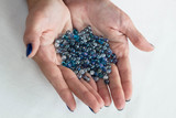 Blue glass beads on woman hands