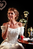 Happy girl in a wedding dress sits at table. On the table box with a wedding ring and burning candle.