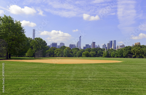Green grass and baseball field of Central Park with Manhattan skyline and blue s Poster