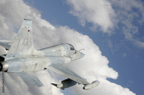 Fighter Jet Against White Clouds And Blue Sky Poster