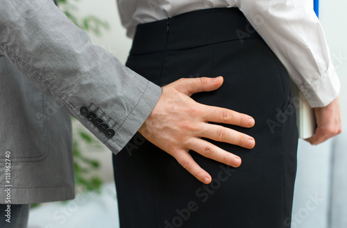 Sexual harassment at work. Man touching woman's butt.
