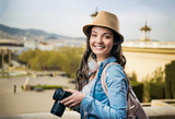 Tourist girl in denim shirt with camera, sunny city