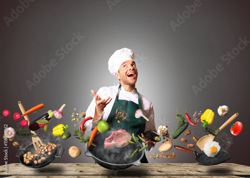 Wall mural Chef juggling with vegetables and other food in the kitchen