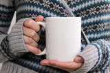 Girl in a warm cardigan is holding white mug in hands.