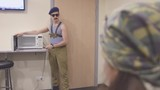 Man in marine shirt and cap, sunglasses open microwave with knife in hands. Explain something to people. Surrealism