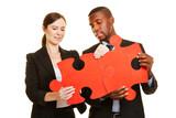 Mann und Frau verbinden rote Puzzleteile