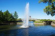 Early morning photo of a fountain in Regina Saskatchewan's Wascana Park with a rainbow in the spray. Landscape view with a footbridge and the provincial legislature in the distance.