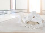 Fototapety Towels in basket on wooden table over defocused bathroom background