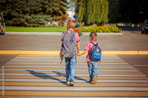 Poster Two boys with backpack walking, holding on warm day  on the road