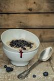 Schüssel mit Porridge und Heidelbeersosse auf einem alten Holzuntergrund