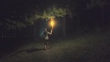 Brave girl traveling the night forest holding a fiery torch in hand. Slow motion.