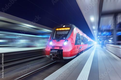 Nowożytny wysokiej prędkości czerwony pociąg pasażerski przy nocą