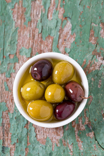 Poszter olives in a bowl on wooden surface