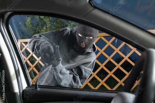 Poster An armed man in the mask threatening pistol to the driver of the car