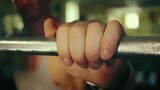 Athlete takes the Barbell in the Gym hand close-up