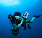 Underwater Photographer scuba diving with camera in sea