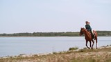 Tracking shot of fast brown horse with smiling woman galloping on shore near water