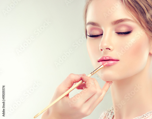 Zdjęcia Hand of make-up master, painting lips of young beautiful model