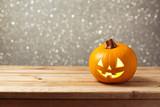 Jack lantern pumpkin on wooden table ober bokeh background. Halloween holiday celebration