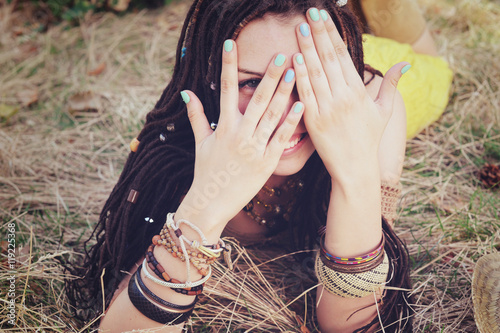 Poster Joyful indie style woman with dreadlocks hairstyle, have a fun closing her face