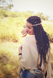 Joyful boho style girl portrait, dressed in knitted poncho and headband have a fun against sunny autumn park,