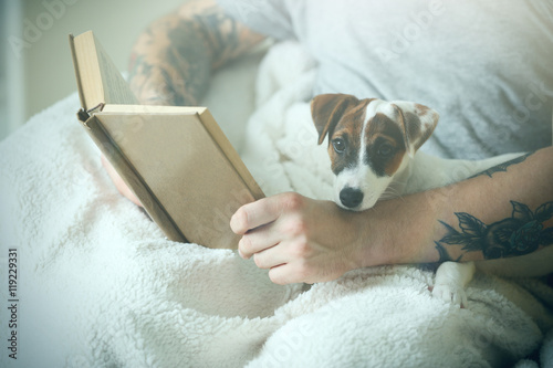 Foto op Plexiglas Kiev Man with cute dog reading book