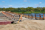 pontoon bridge with a wooden deck and fences across the river in Sunny day on background of blue sky